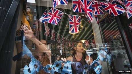 Employees hang a sign celebrating the royal birth in the window of the British-themed restaurant in New York on 22 July 2013