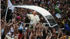 Pope Francis waves to the crowd near the Metropolitan Cathedral in the Popemobile in Rio de Janeiro, Brazil