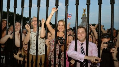 The large waiting crowds cheers at Buckingham Palace