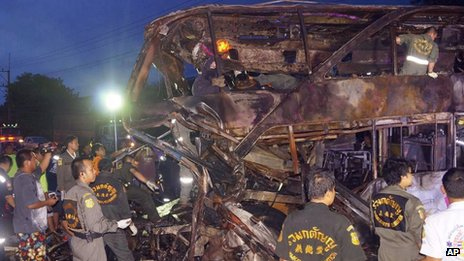 Rescue workers at the charred wreckage of a double-decker passenger bus after an accident in Saraburi province, northeast of Bangkok, Thailand 23 July 2013