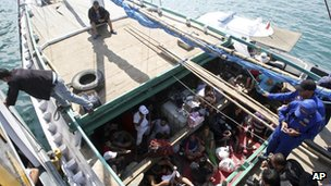 File photo:  Iranian asylum seekers who were caught in Indonesian waters while sailing to Australia, sit on a boat, at Benoa port in Bali, Indonesia, 12 May 2013