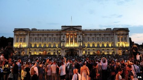 Crowds gather to see an easel in the forecourt of Buckingham Palace