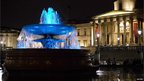 The fountains in Trafalgar Square lit up blue