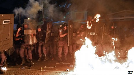 Police shield themselves from Molotov cocktails thrown during a protest in Rio on 22 July 2013
