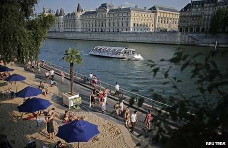 People relax on a temporary urban beach in Paris, near the Pont Neuf bridge, 20 July