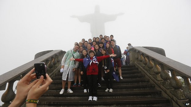 Young people pose for pictures under Christ the Redeemer statue, Rio de Janeiro