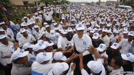 Sam Rainsy (centre), president of the Cambodia National Rescue Party, is surrounded by his supporters in Kampong Speu province 20 July 2013