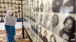 A female Cambodian-Muslim looks at portrait photos of victims of the Khmer Rouge regime displayed for tourists at the Tuol Sleng Genocide Museum in Phnom Penh on 4 June 2013