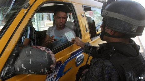 An Iraqi policeman checks a driver's documents in Baghdad