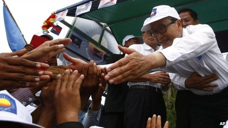 Sam Rainsy, president of the Cambodia National Rescue Party, shakes hands with his party supporters during an election campaign rally at Kampong Speu province, west of Phnom Penh, Cambodia, 20 July 2013