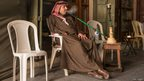 Qatari gentleman relaxing in the Souk smoking his Shisha pipe.