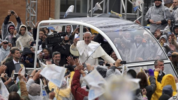 The pontiff waves to pilgrims from his Popemobile as he arrives at the Aparecida Basilica