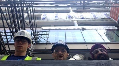 3 construction workers look out from a building site