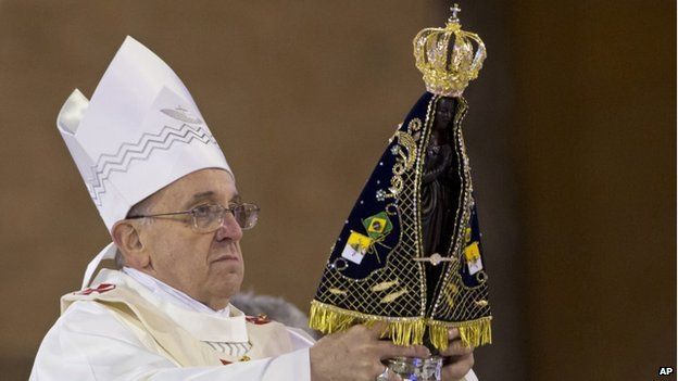 The Pope holds a statue of Our Lady of Aparecida, the patron saint of Brazil, during his Mass in Brazil