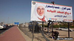 Workers hang a campaign poster of a candidate ahead of the parliamentary elections