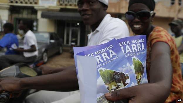 Supporters of presidential candidate Cheick Modibo Diarra distribute campaign flyers from the back of a moped as they ride in a campaign caravan through the streets of Bamako, Mali on Saturday 20 July 2013.