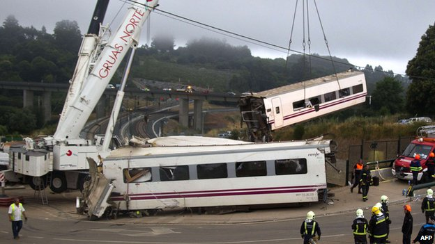 A crane removes one of the derailed train carriages at the site of a train accident near Santiago de Compostela