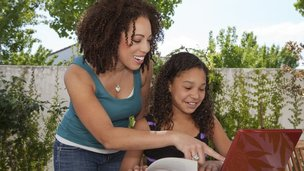Mother and daughter looking at laptop screen