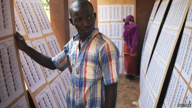 A man searches for his name on a list of eligible voters at an election centre in Bamako, Mali - 23 July 2013