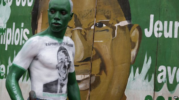 A performer wears body paint depicting presidential candidate Soumaila Cisse as he walks past a campaign sign, during a rally for Cisse in Bamako, Mali, on Saturday 20 July 2013