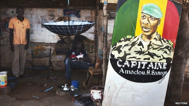 Men sit next to a painting of the ex-junta leader Amadou Haya Sanogo in Bamako in Mali on 16 July 2013