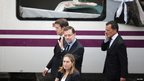 Mariano Rajoy walks past the damaged train