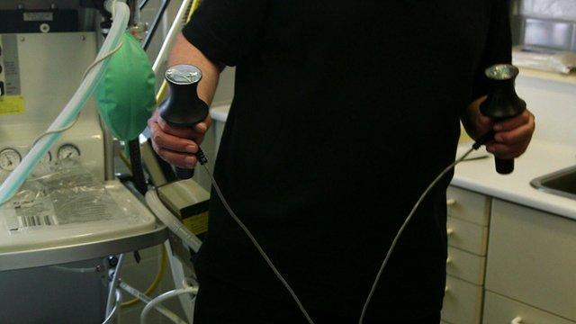 Medic holding ECT electrodes