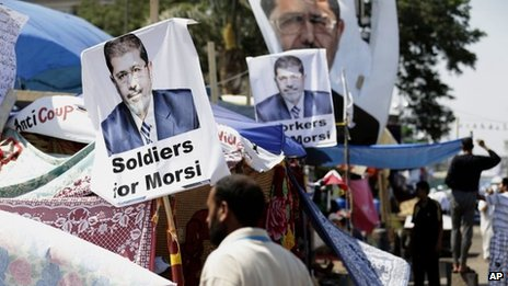 A supporter of Egypt's Islamist President Mohammed Morsi in front pictures of President Mohammed Morsi at Nasr City