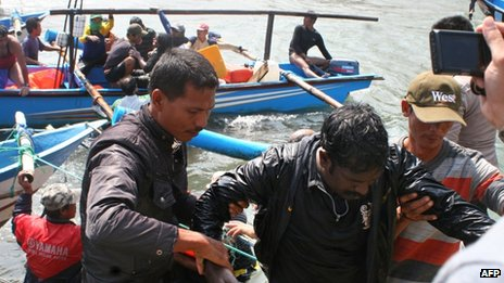 Rescuers assist a survivor on arrival at the wharf of Cidaun, West Java on 24 July 2013 after an Australia-bound boat carrying asylum-seekers sank off the Indonesian coast