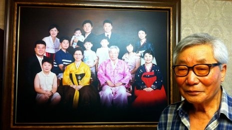 Kim Kyo-yong stands in front of a photo of his South Korean family