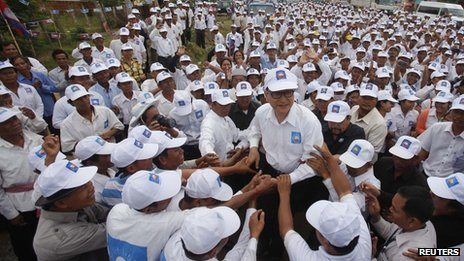 Sam Rainsy (C), president of the Cambodia National Rescue Party (CNRP), is surrounded by his supporters in Kampong Speu province 20 July 2013
