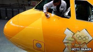 A man cleans a London 2012-branded BA aircraft