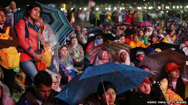 Young faithful listen to Pope in the rain on Copacabana beach