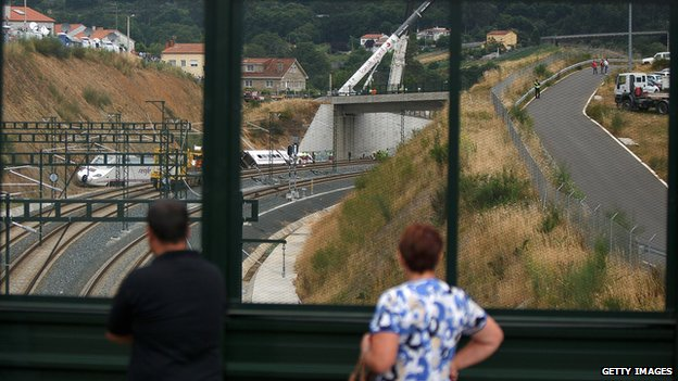 People watch the site of a train crash that killed at least 80 people on 25 July