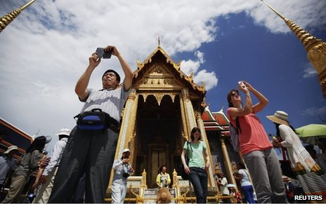 Tourists take photos at the Grand Palace in Bangkok