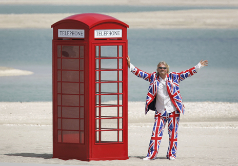 Richard Branson in union jack suit standing next to telephone box