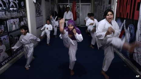 In this Monday, April 8, 2013 photo, Pakistani schoolgirls, Shazil Ishtiaq, 12, right, and Aysha Huma, 9, centre, attend a Karate class at Shotokan Karate School in Islamabad, Pakistan.