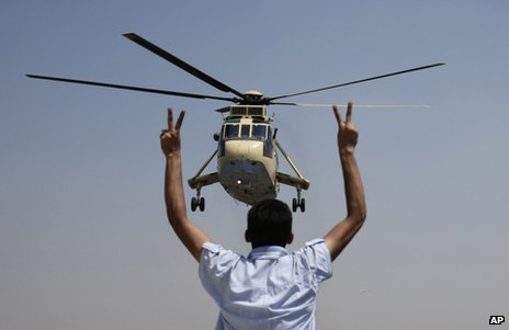 A man flashes the Victory sign at an army helicopter in Cairo, 26 July