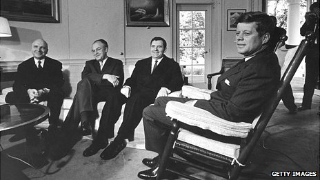 President John F Kennedy sitting in a big rocking chair while three Russian officials sit lower on a couch