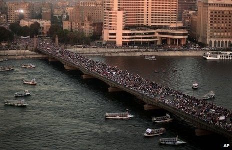 Anti-Morsi demonstrators cross a bridge in Cairo, 26 July