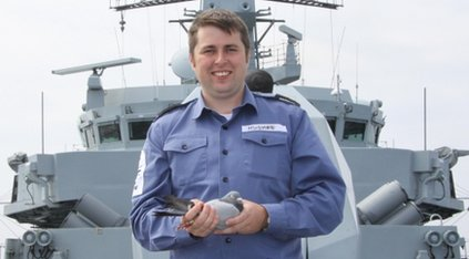 Leading seaman William Hughes with the lost pigeon