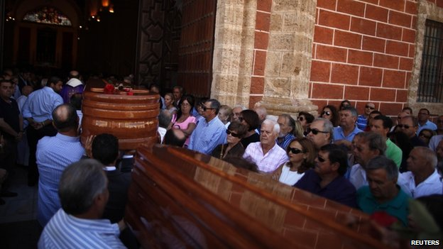 People carry the coffins of two of the victims of Wednesday's train crash near Santiago de Compostela, outside Iglesia Mayor church in San Fernando on 27 July, 2013