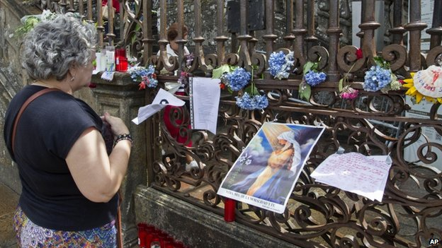 A woman prays for the train crash victims  in front of a makeshift shrine outside the cathedral in Santiago de Compostela on 27 July 2013.