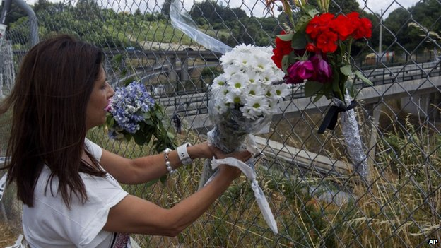 A woman fixes a bunch of flowers to a fence above the railway tracks where a train crashed near Santiago de Compostela, Spain. Photo taken Saturday 27 July, 2013