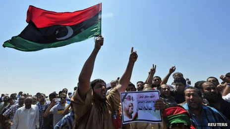 Men hold up a picture of prominent Libyan political activist Abdelsalam al-Mismari during his funeral in Benghazi on 27 July, 2013