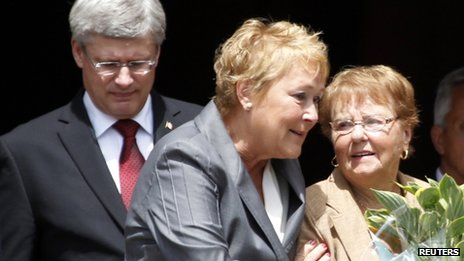 Quebec Premier Pauline Marois (C) comforts a mourner as she and Canadian Prime Minister Stephen Harper (L) walk out of Sainte-Agnes Church following the memorial service to honour the victims of the train derailment in Lac Megantic, Quebec on 27 July, 2013