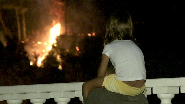 Young girl looks on at flames in Barcelona