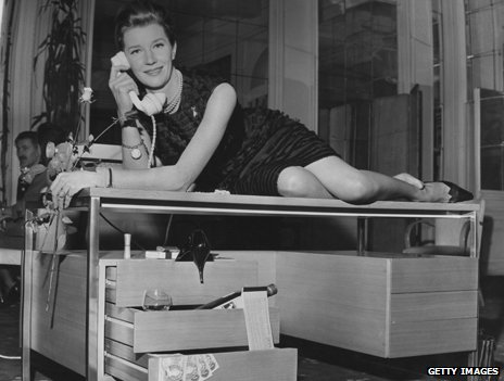 Actress Lois Maxwell reclining on a desk and holding a telephone to her ear