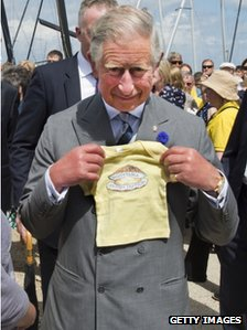 Prince Charles is given a present for his grandson Prince George of Cambridge at the Whitstable Oyster Festival