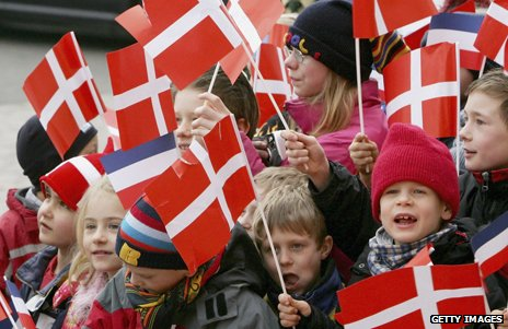 Danish children crowded together waving Danish flags